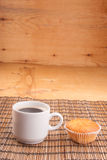 Espresso coffee in a white china cup over wood. Espresso coffee in a white china cup and cupcake over wooden mat royalty free stock photo