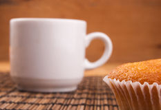 Espresso coffee in a white china cup over wood. Espresso coffee in a white china cup and cupcake over wooden mat stock photography