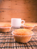 Espresso coffee in a white china cup over wood. Espresso coffee in a white china cup and cupcake over wooden mat stock photos