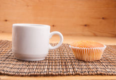 Espresso coffee in a white china cup over wood. Espresso coffee in a white china cup and cupcake over wooden mat stock images