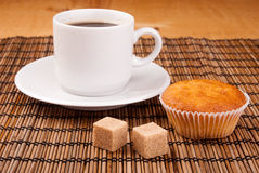 Espresso coffee in a white china cup over wood. Espresso coffee in a white china cup and cupcake over wooden mat royalty free stock photos