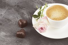 Espresso coffee in a white cup, a pink rose and chocolates on a Royalty Free Stock Images