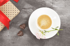 Espresso coffee in a white cup, a pink rose, a gift with a red t Royalty Free Stock Photo