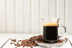 espresso Copo de vidro do café com feijões de café em um backgr claro fotografia de stock royalty free