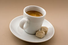 Espresso Cup. With sugar cubes over a light brown background royalty free stock photos