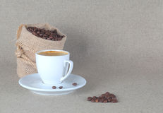 Espresso cup with coffee beans bag on back. Image royalty free stock photo