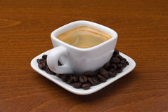 Espresso cup with coffee beans on table Stock Photos