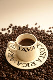 Espresso Cup of Coffee with Costa Rica Arabica Beans. Small espresso cup of strong dark Costa Rican Arabica Coffee surrounded by fresh coffee beans with Royalty Free Stock Photos