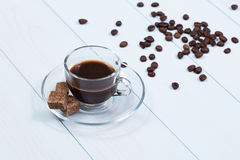 Espresso cup of coffee, sugar and beans. On a wood table Royalty Free Stock Photo