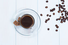 Espresso cup of coffee, sugar and beans. On a wood table Stock Image