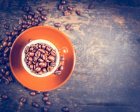 Espresso cup full of coffee beans on rustic wooden background, top view,close up Stock Image