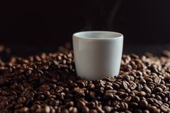 Espresso cup full of coffee on the grains pile. Italian traditional morning short drink on breakfast. Close-up. Toned Royalty Free Stock Photos