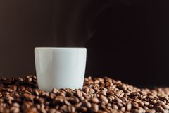 Espresso cup full of coffee on the grains pile. Italian traditional morning short drink on breakfast. Close-up. Toned Stock Images