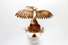 Espresso cup with hand drawing phoenix bird. Coffee art or creative concept. Top view.  royalty free stock image