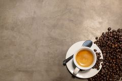 Espresso in a cup of hot coffee and coffee beans on concrete polishing floors cement background in loft style in a cafe shop, stock images