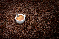 Espresso cup with a spoon on coffee beans Stock Photography