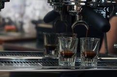 Espresso, das in zwei Schußgläser ausläuft Lizenzfreie Stockbilder
