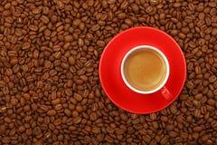 Espresso in der roten Schale mit Untertasse auf Kaffeebohnen Lizenzfreie Stockfotos