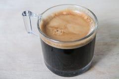 Espresso in einem Schnapsglas gesetzt auf eine Holzoberfläche Stockbilder