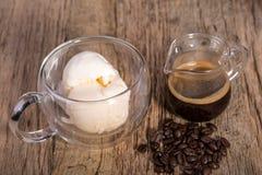 Espresso en Vanilleroomijs in glas Italiaans dessert met dubbele muren, met koffiebonen op het rustieke houten lusje Stock Afbeelding