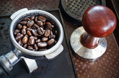 Espresso filter filled with coffee beans and tamper Royalty Free Stock Images