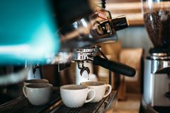 Espresso flows down from the coffee machine in to two cups of coffee royalty free stock images