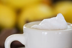 Espresso with foam. White demitasse cup filled with espresso and topped with dollop of foam royalty free stock image