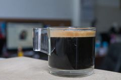 Espresso in a glass placed on a wooden floor. For fresh coffee. The smell of fresh coffee in the glass on top of it Royalty Free Stock Images