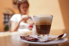 Espresso machiato. Closeup of espresso machiato coffee with woman sat in background Royalty Free Stock Image
