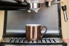 Espresso machine making coffee and pouring in a brown  cup Royalty Free Stock Photography