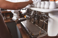 Espresso machine with mugs on it. Kitchen of a local cafeteria with the industrial machine for making beverages. Barista working Stock Photography