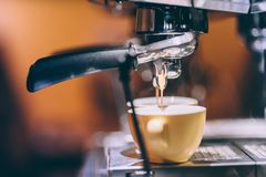 Details of espresso machine pouring and brewing fresh, creamy coffee in local bistro, restaurant or pub Stock Images