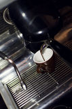 Espresso machine pouring coffee. Close up of an espresso machine pouring coffee in a restaurant Stock Photography