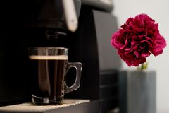 Espresso Coffee With Pink Flower As A Detail. Espresso Machine Pouring Fresh Coffee Into Glass Cup royalty free stock photos