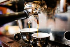 Espresso pouring from coffee machine into cups. Prof. Close-up of espresso pouring from coffee machine into cups. Professional coffee brewing, barista details stock photography