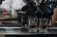 Espresso pouring into two shot glasses. Coffee Royalty Free Stock Images