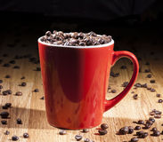 Espresso red cup with coffee beans. Espresso red big cup on a wooden table full of coffee beans Royalty Free Stock Photography