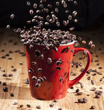 Espresso red cup with coffee beans falling. Espresso red big cup on a wooden table with coffee beans falling inside Royalty Free Stock Photos