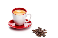 Espresso in red and white cup with coffee beans Royalty Free Stock Image