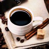 Espresso-Schale auf brauner Serviette mit Zimt und Zucker. Lizenzfreie Stockfotografie