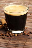 Espresso in a short glass with coffee beans and ci Royalty Free Stock Images