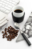 Espresso in small cup with coffee beans. Teaspoon, stylish napkin, keyboard stock photography