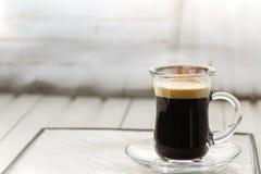 espresso Taza de cristal del café express con los granos de café en un backgr ligero imagenes de archivo