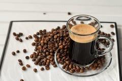 espresso Taza de cristal del café express con los granos de café en un backgr ligero fotografía de archivo