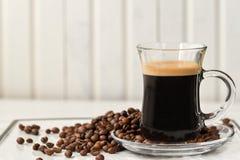 espresso Taza de cristal del café express con los granos de café en un backgr ligero imagen de archivo