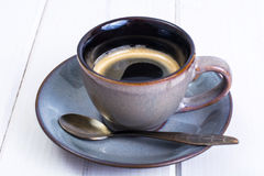 Espresso in vintage cup and saucer on white wooden background Stock Photo