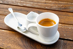 Espresso in white ceramic cup next to milk and spoon on rustic w. Ooden table Stock Images