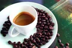 Espresso in white cup. Hot espresso, coffee in white cup and disk with coffee bean royalty free stock photo
