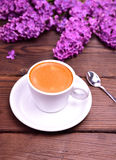 Espresso in a white cup with saucer and spoon. Behind a bouquet of purple lilac, top view Royalty Free Stock Photo