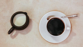 Espresso in white cup and saucer with spoon, milk in jar. On grunge vintage background Stock Photo
